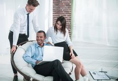 Successful businessman with his assistants in a discussion of the information from the laptop. Office life stock image