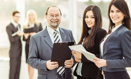 Successful businessman and his two assistants with documents on the background of the modern office. Businessman and his two assistants with documents on the stock image