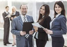 Successful businessman and his two assistants with documents on the background of the modern office. Businessman and his two assistants with documents on the royalty free stock image