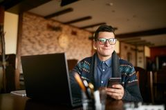 Successful businessman holding mobile modern smartphone. Happy hipster with a modern phone enjoys pleasant news. Smiling. Young man in glasses with laptop on stock photo