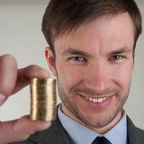 Successful businessman holds a pile of coins in front of him. Royalty Free Stock Images