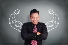 Successful Businessman with Inner Power Strength. Portrait of successful young Asian businessman smiling with crossed arms standing over grey wall with imaginary royalty free stock photos