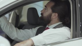 Portrait attractive confident bearded businessman sitting in the vehicle and inspects newly purchased auto from the car. Successful businessman inspects newly stock footage
