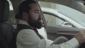 Portrait attractive confident bearded businessman sits in the vehicle and inspects newly purchased auto from the car. Successful businessman inspects newly stock video footage