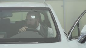 Portrait attractive confident bearded businessman sits in the vehicle and inspects newly purchased auto from the car. Successful businessman inspects newly stock video