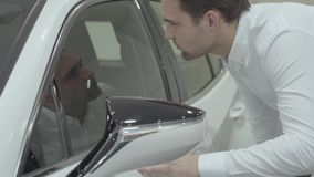 Portrait successful businessman inspects newly purchased auto from the car dealership. Car showroom. Advertising concept stock footage