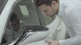 Successful businessman inspects newly purchased auto from the car dealership. Car showroom. Advertising concept. stock video