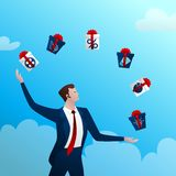 Successful businessman juggles with gifts. The successful businessman with a happy smile juggles boxes with gifts on a blue background and clouds. Concept idea Royalty Free Stock Image