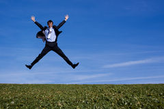 A successful businessman jumping. A happy, successful businessman jumps for joy on a hillside Stock Images