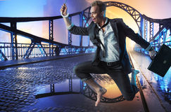 Successful businessman jumping on the bridge Stock Image