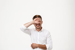Successful businessman laughing, hiding eyes behind hand over white background. Stock Photography