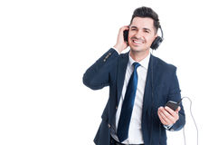 Successful businessman listening music from mobile phone and smi Stock Photos