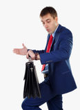 Successful businessman looking at his watch. In his hand is holding portfoliol Royalty Free Stock Photo