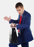 Successful businessman. Looking at his watch. In his hand is holding portfoliol Royalty Free Stock Photo