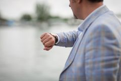 Close-up man with watch on a hand. Businessman checking time on a blurred city background. Business concept. Copy space. stock photography
