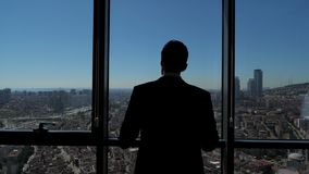 Successful businessman is looking at panoramic city view from his modern apartment. Silhouette of successful young businessman in suit is looking at window. He stock video