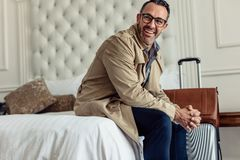 Successful businessman with luggage sitting in hotel room bed and looking away. Mature businessman on business trip royalty free stock photo