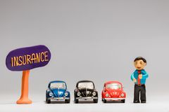 A businessman made from plasticine next to three cars and an insurance sign , on white background royalty free stock photo