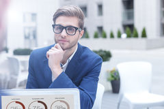 Successful businessman is making serious decision. Cheerful young man has a business meeting in cafe. He is sitting at table near a laptop and thinking seriously Royalty Free Stock Photography