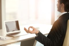 Successful businessman meditating at work desk in modern office. Back view over shoulder of calm businessman meditating in yoga pose in front of laptop in royalty free stock photos