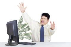 Successful businessman with money from computer Royalty Free Stock Image