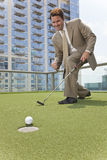 Successful Businessman Playing Rooftop Golf Royalty Free Stock Photography