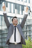 Successful businessman pointing upwards outside office building Stock Images