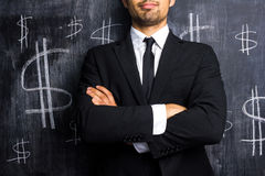 Successful businessman posing in front of dollar signs. On blackboard royalty free stock image
