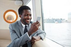 Notification. Successful businessman reading notification in smartphone by window of steamship on rainy day Royalty Free Stock Photography