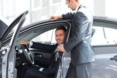 Successful businessman, receiving the keys to the car from the seller in the showroom Royalty Free Stock Image