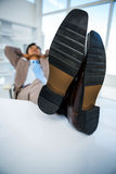 Successful businessman relaxing with his feet on his desk Royalty Free Stock Image