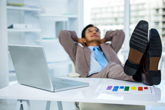 Successful businessman relaxing with his feet on his desk Stock Image
