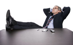Successful businessman relaxing over his desk Stock Images