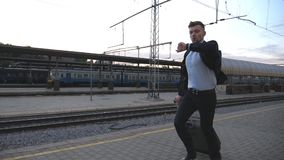 Successful businessman running through railway station and looking at watch. Young man is late for train. Business