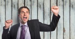 Successful businessman screaming while clenching fists against wooden wall. Digital composite of Successful businessman screaming while clenching fists against Stock Image