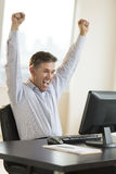 Successful Businessman Screaming While Using Computer. Successful mature businessman with arms raised screaming while using computer in office Royalty Free Stock Photo