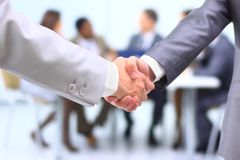 Successful businessman shaking. Two successful businessman shaking hands in front of corporate team at office Royalty Free Stock Image