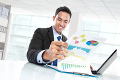 Successful businessman showing growth chart and smiling Stock Images