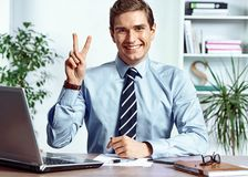 Successful businessman showing victory sign. Photo of young man working in the office. Business concept Royalty Free Stock Images