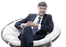 Successful businessman sits in a soft comfortable chair. Businessman sits in a soft comfortable chair. life style Royalty Free Stock Photo