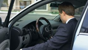 Successful businessman sitting on driver seat, taking keys to car just bought. Stock footage stock video footage