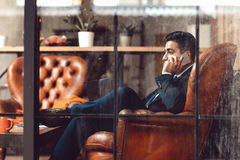 Successful businessman sitting in firm. Side view on man talking on phone. Professional activity. Advising. Counseling. Trading royalty free stock photo