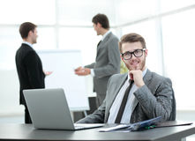 Successful businessman sitting at the table with an open laptop Stock Photos