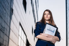 Successful businessman, standing against the backdrop of buildings holding  folder with sales charts. City business woman working. Royalty Free Stock Images