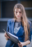 Successful businessman standing on background  buildings looking at the folder charts of sales. City business woman working. Successful businessman standing on Royalty Free Stock Photo