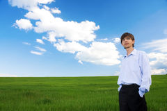 Successful businessman standing on grassland. Successful businessman standing on green grassland under blue sky stock photography