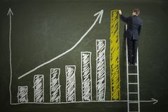 Successful businessman is standing on ladder and drawing growing graph of profit. Royalty Free Stock Photo