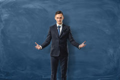 Successful businessman is standing with open arms isolated on blue chalkboard background Royalty Free Stock Photo