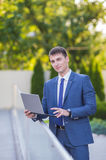 Successful businessman standing in the street Stock Images