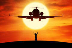 Successful businessman standing under flying plane Royalty Free Stock Photos